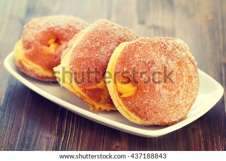 donuts with cream on white dish on brown wooden background - stock photo