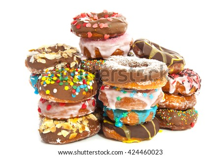Donuts with sweets on a pile isolated over white - stock photo