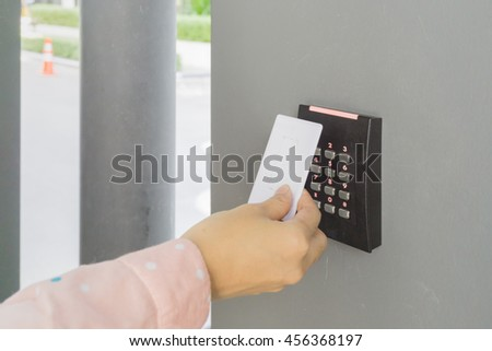 Door access control with a hand inserting key card to lock and unlock door. Security system concept. - stock photo