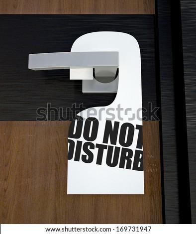 Door hanger Do not disturb message hanged on handle - stock photo