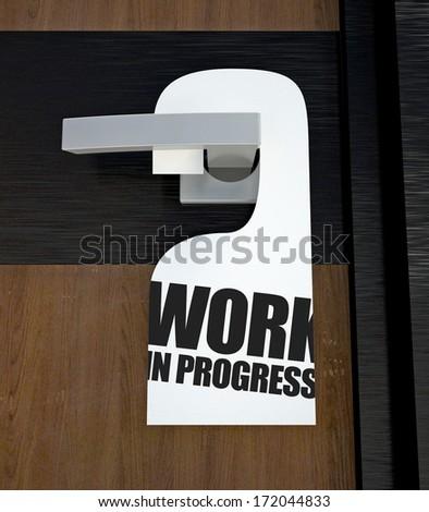 Door hanger Work in progress message hanged on handle - stock photo