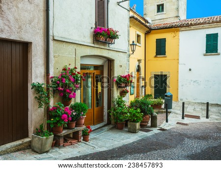 Door in an old house decorated with flower pots and flowers at night - stock photo