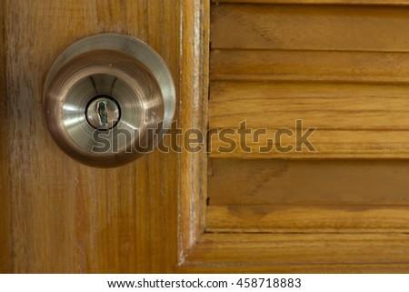 door knob and keyhole on wooden door, close up image - stock photo