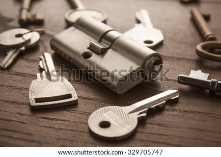 door lock with keys on wooden surface - stock photo