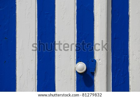 Door of a beach holiday house painted in a typical striped blue and white pattern - stock photo