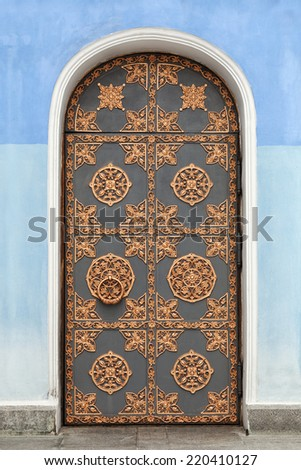 Door of an old building decorated with golden ornaments - stock photo