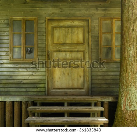 Door of wooden house with stairs in the forest - stock photo