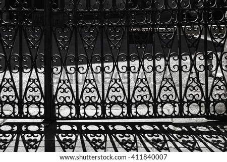 door with  wrought iron bars and shadows on the pavement - stock photo