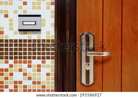 Doorbell Ring Button On The Wall And Metal Door With Handle Close-up - stock photo