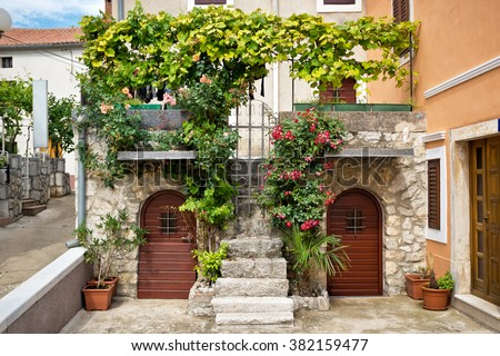 Doors and balconies full of of green plants and flowers in a traditional mediterranean house - stock photo