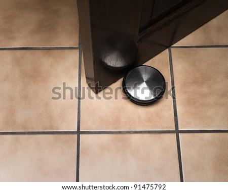 Doorstop holding door on ceramic floor - stock photo