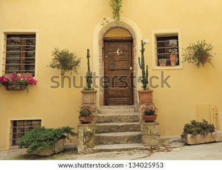 doorway to the house decorated with cacti plants, Tuscany, Italy - stock photo