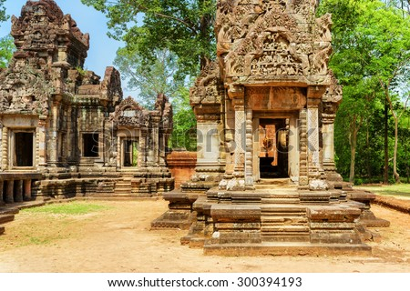Doorway with carving of ancient Thommanon temple in enigmatic Angkor, Siem Reap, Cambodia. Mysterious Thommanon nestled among rainforest. Amazing Angkor is a popular tourist attraction. - stock photo