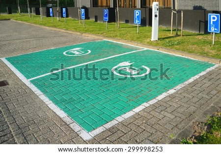 DORDRECHT, NETHERLANDS - JULY 13, 2015:Plug-in hybrid and electric vehicle designated, green-painted parking spaces with charging station for guests at a modern Postillion hotel.   - stock photo