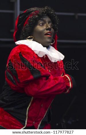 DORDRECHT, NETHERLANDS - NOVEMBER 12: Woman dressed as Zwarte Piet entertaining children on Saint Nicolas parade on November 12, 2011 in Dordrecht, Netherlands. - stock photo
