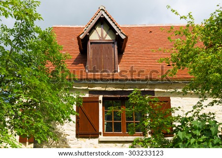 Dormer window located on the red clay roof of a French country house - stock photo