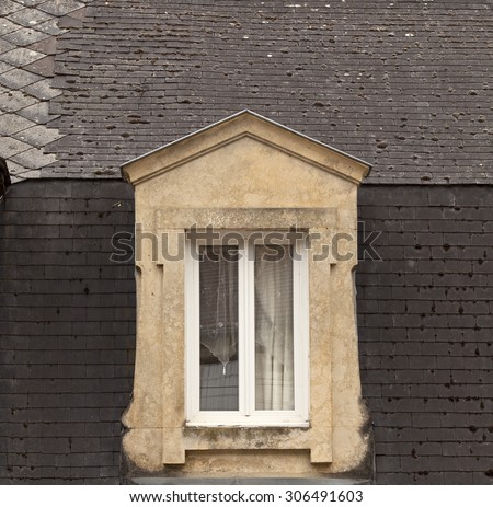 Dormer window with delicate curtains. A stone dormer window stands in contrast to the heavy brown tiles on the roof. The window is dressed with delicate french curtains. Found in France. - stock photo