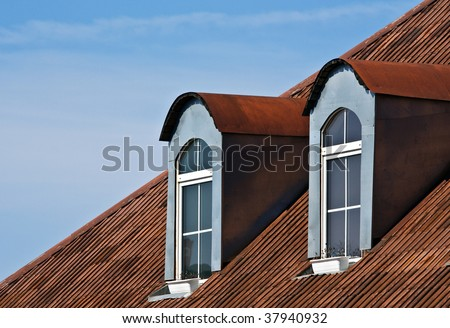 Dormer windows and red tiled metal rooftop - stock photo