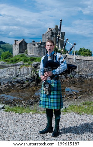 DORNIE, SCOTLAND - June 7, 2014: A bagpipe player with traditional kilt in front of Eilean Donan, the most famous castle in Scotland, on June 7, 2014 in Dornie, Scotland, United Kingdom.  - stock photo