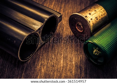 Double-barreled shotgun barrel and two green cartridges. Close up view, image vignetting and the yellow-blue toning - stock photo