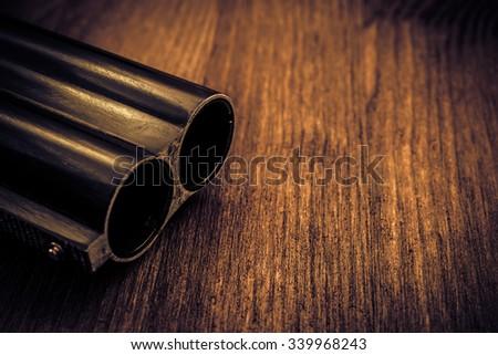 Double-barreled shotgun barrel close-up. Image vignetting and the yellow-blue toning - stock photo