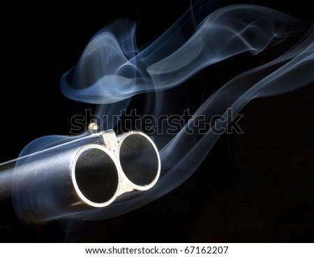 double barreled shotgun with both of the barrels smoking - stock photo