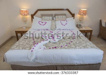 Double bed with love heart from rose petals in bridal suite of a hotel - stock photo