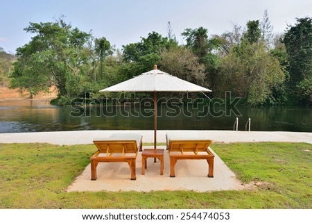 Double chairs on grass beside a river - stock photo