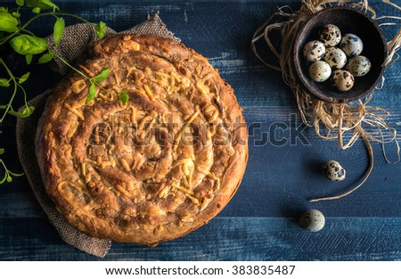 Double cheese pie and quail eggs on wooden background,Easter concept  - stock photo