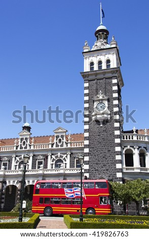 Double deck bus by historic Railway Station in Dunedin city (New Zealand). - stock photo
