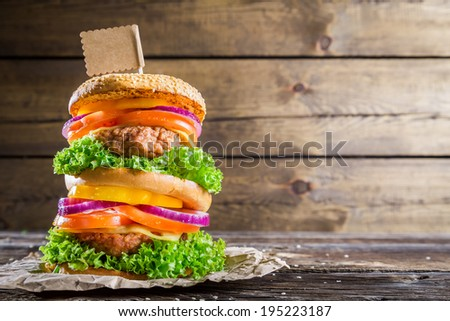 Double-decker burger on wooden background with space to menu - stock photo