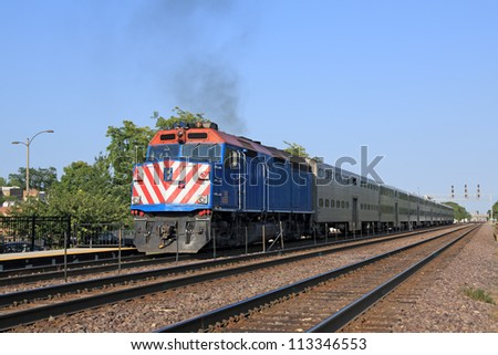 Double-decker commuter train arriving at a station in the suburbs - stock photo