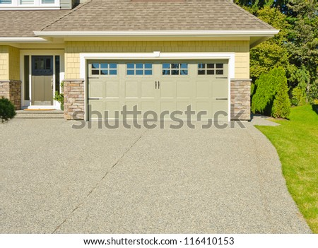 Double doors garage with wide and long driveway. - stock photo