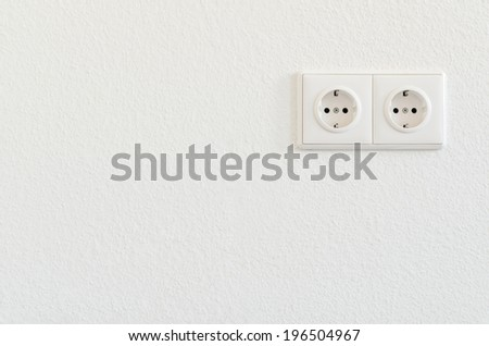 double electrical socket on white wallpaper  - stock photo