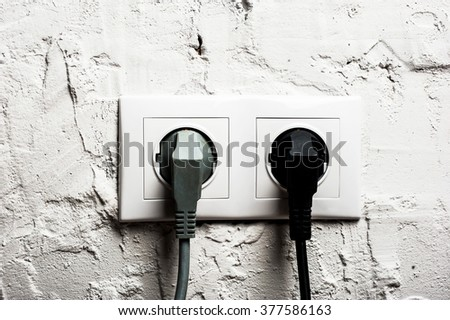 Double electrical socket with plugged cables on brick wall - stock photo