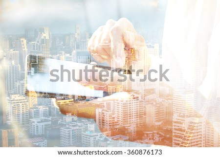 Double exposed of business man using smartphone and city scape. - stock photo
