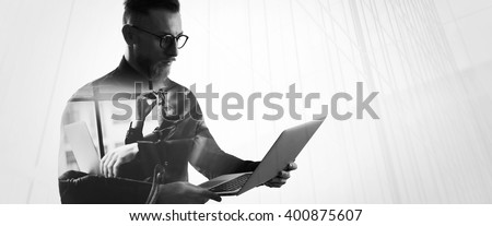 Double exposure bearded businessman wearing shirt and glasses,holding contemporary notebook hands. Portrait young banker using laptop in modern office, skyscraper background. Wide, black,white - stock photo