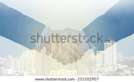 double exposure handshake between businessman on a construction building background - stock photo