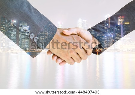 Double exposure handshake of business peoples on the colorful night city background.   - stock photo