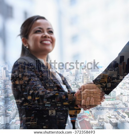 Double exposure handshake on city background. - stock photo