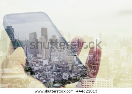 Double exposure image of using smart phone with cityscape background, Communication technology concept - stock photo