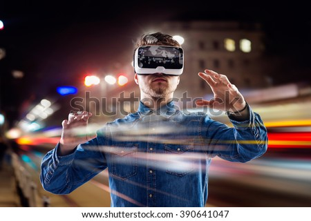 Double exposure, man wearing virtual reality goggles, night city - stock photo