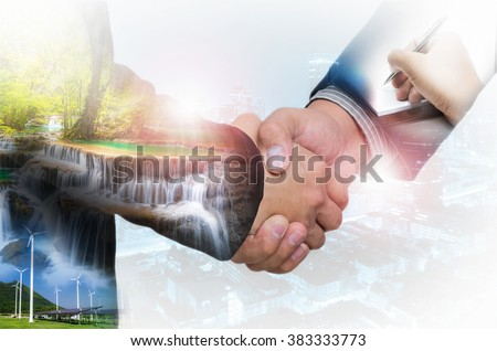 Double Exposure of a businessman handshake on the background blurred downtown nightlife. Concept of an agreement green energy. - stock photo