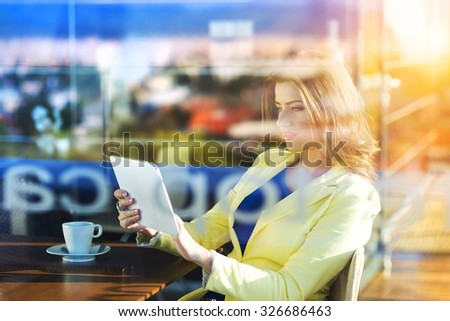 Double exposure of an attractive young woman with tablet in a cafe - stock photo