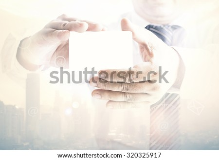 Double exposure of asian business man hands holding a blank business card and blurred city on sunset background. - stock photo