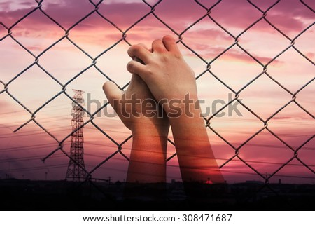 double exposure of asian girl hand hold jail on sunset at the town background - stock photo