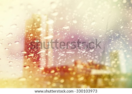 double exposure of blurred cityscape and raindrop with color filter          - stock photo