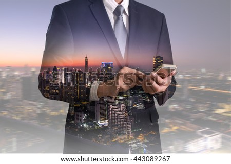 Double exposure of business man hand hold and touch screen smart phone, mobile and night cityscape as telecommunication and technology concept. - stock photo