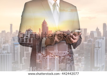 Double exposure of business man hand hold and touch screen smart phone, mobile, cityscape and sunset as telecommunication and technology concept. - stock photo