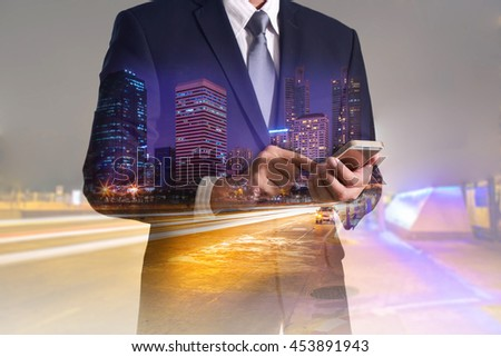 Double exposure of business man hand hold and touch screen smart phone, mobile, urban, city and street at night as business, telecommunication and technology concept. - stock photo